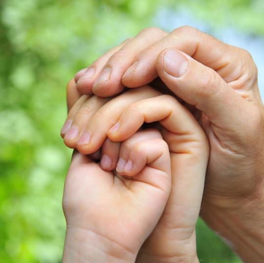 Drei Hände, die sich halten