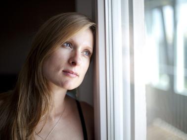 Eine Frau schaut nachdenklich aus einem Fenster