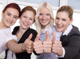 Vier Frauen, die das Zeichen Daumen hoch geben
