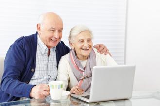 Ein älteres Paar sitzt vor einem Computer