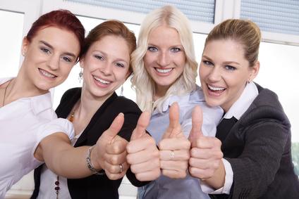 Vier Frauen lachen in die Kamera und zeigen Daumen hoch
