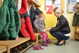 Mutter holt Kind im Kindergarten ab
