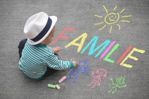 Kind malt mit Kreide auf Straße
