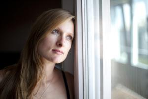 Frau schaut nachdenklich aus Fenster
