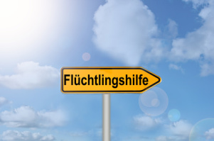 "Gelber Wegweiser ""Flüchtlingshilfe"" vor blauem Himmel"