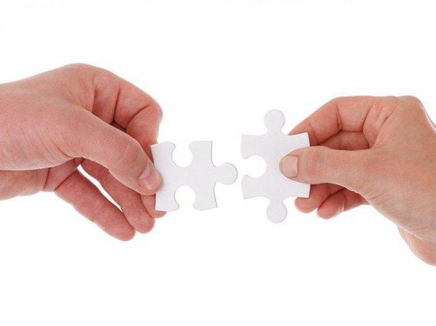 Zwei Hände verbinden zwei Puzzleteile