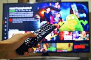 Fernbedienung vor Fernsehbildschirm mit Streamingdienst